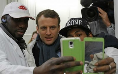 French presidential candidate Emmanuel Macron, center, poses for a selfie with employees as he visits the meat pavilion at the Rungis wholesale food market south of Paris, April 18, 2017. (Philippe Wojazer; Pool via AP)