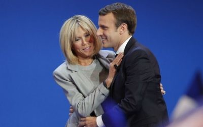 French centrist presidential candidate Emmanuel Macron and his wife Brigitte hug as he addresses his supporters at his election day headquarters in Paris , Sunday April 23, 2017. (AP/Christophe Ena)