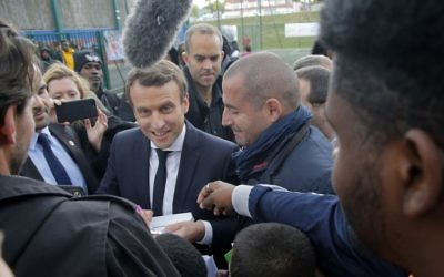 French presidential election candidate Emmanuel Macron signs autographs during a campaign visit to Sarcelles, north of Paris, Thursday, April 27, 2017. (Michel Euler/AP)