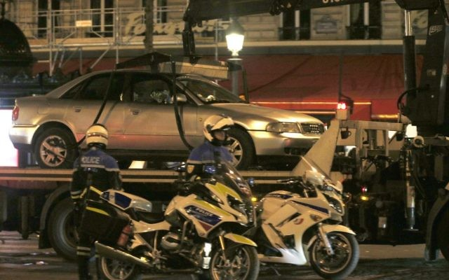 The car belonging to an attacker is towed away from the Champs-Elysees avenue in Paris, France, after a fatal shooting in which a police officer was killed along with the attacker, Friday, April 21, 2017. (AP Photo/Thibault Camus)