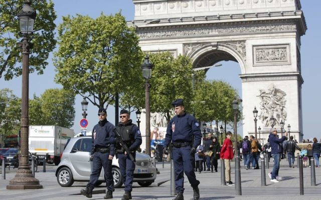 French riot police officers patrol on the Champs Elysees boulevard, with the Arc of Triomphe in background, in Paris, Friday, April 21, 2017. (AP Photo/Christophe Ena)