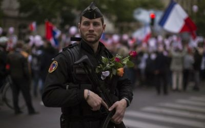 A French riot police officer carries flowers given to him by a demonstrator, in Paris, Saturday, April 22, 2017, a day before the country begins its two-round presidential election. (AP Photo/Emilio Morenatti)