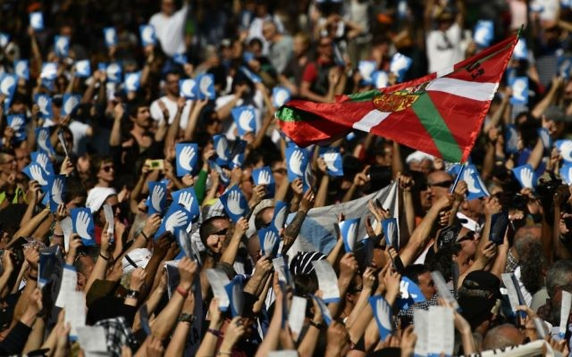 Pro independence Basque followers hold up the symbol of the day called ''Artisans of the Peace'' close to a Basque flag during a meeting after the announcement that ETA handed over its arms in Bayonne, southwestern France, Saturday, April 8, 2017.(AP Photo/Alvaro Barrientos)