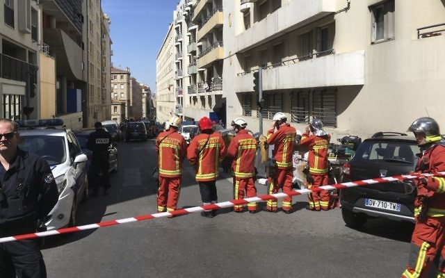 """A police officer and rescue workers cordon off a street during searches in Marseille, southern France on April 18, 2017 after French police thwarted an imminent """"terror attack."""" (AP Photo/Claude Paris)"""
