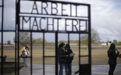 People stand behind the gate with the inscription 'Arbeit macht frei' (work sets you free) at the Sachsenhausen Nazi death camp in Oranienburg, about 35 kilometers north of Berlin, April 23, 2017. Commemorations will be held on Sunday on the occasion of the 72th anniversary of the liberation of the camp. (AP/Markus Schreiber)