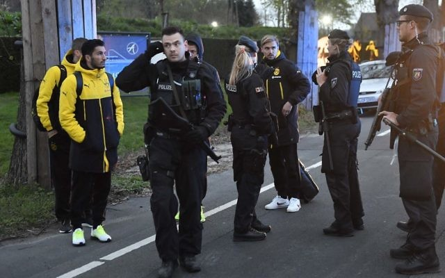 Dortmund's Marcel Schmelzer talks to police officers outside the team bus after it was damaged in an explosion before the Champions League quarterfinal soccer match between Borussia Dortmund and AS Monaco in Dortmund, Germany, April 11, 2017. (AP Photo/Martin Meissner)