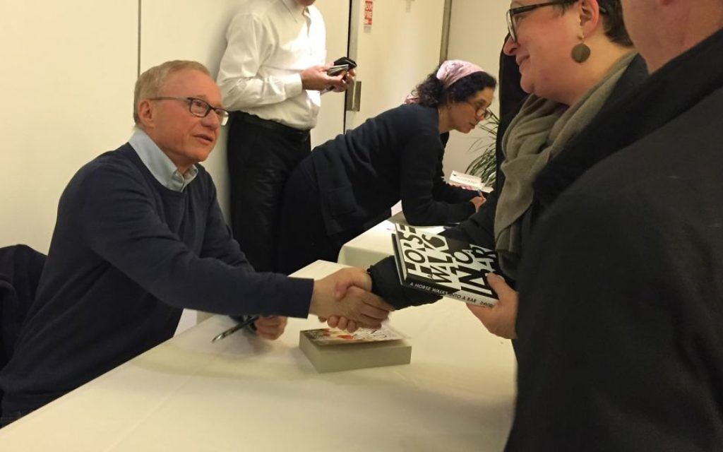 Author David Grossman signs copies of 'A Horse Walked into a Bar' at a April 2, 2017, Times of Israel event in Jerusalem. (Amanda Borschel-Dan/Times of Israel)
