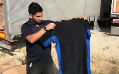 A Defense Ministry worker displays a wet suit found hidden in a shipment of sporting gear that was bound for the Gaza Strip on April 3, 2017. (Defense Ministry)
