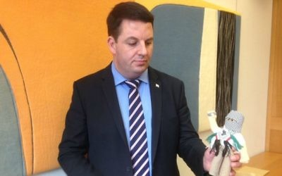 British MP Andrew Percy holds a terror doll teaching aid used in Palestinian schools. (Jenni Frazer/ Times of Israel)