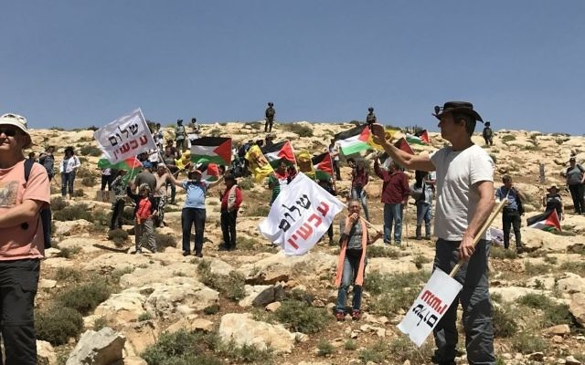 Demonstrators wave Palestinian and Peace Now flags at West Bank protest against settler violence near Michmash Junction, April 28, 2017. (Times of Israel/Jacob Magid)