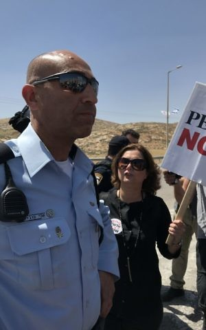 Holding a sign of the Peace Now NGO, Meretz MK Michal Rozen argues with an Israel Police officer during a West Bank demonstration against settler violence on April 28, 2017. (Times of Israel/Jacob Magid)