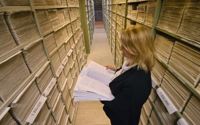 Anna Meier-Osinski, Head of Tracing Investigations into Nazi Victims Branch, among the 3 million correspondence files of the ITS. (Uwe Zucchi/ITS)