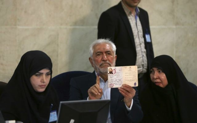Former Iranian oil minister Mohammad Gharazi (center) shows his inked finger and identification while registering his candidacy for the May 19 presidential elections, accompanied by his wife Zohreh (right), at the Interior Ministry in Tehran, Iran, April 13, 2017. (AP/Vahid Salemi)
