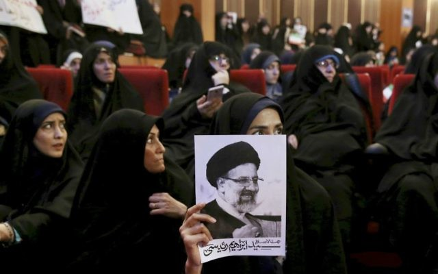 An Iranian holds up a poster of Iranian cleric Ebrahim Raisi, a conservative presidential candidate in the upcoming presidential election, at a campaign rally in Tehran, Iran, Wednesday, April 26, 2017. (AP Photo/Ebrahim Noroozi)