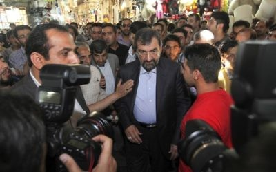 In this file photo taken on Tuesday, May 28, 2013, Iranian presidential candidate Mohsen Rezaei, center, walks through the old main bazaar of Tehran. (AP Photo/Vahid Salemi, File)