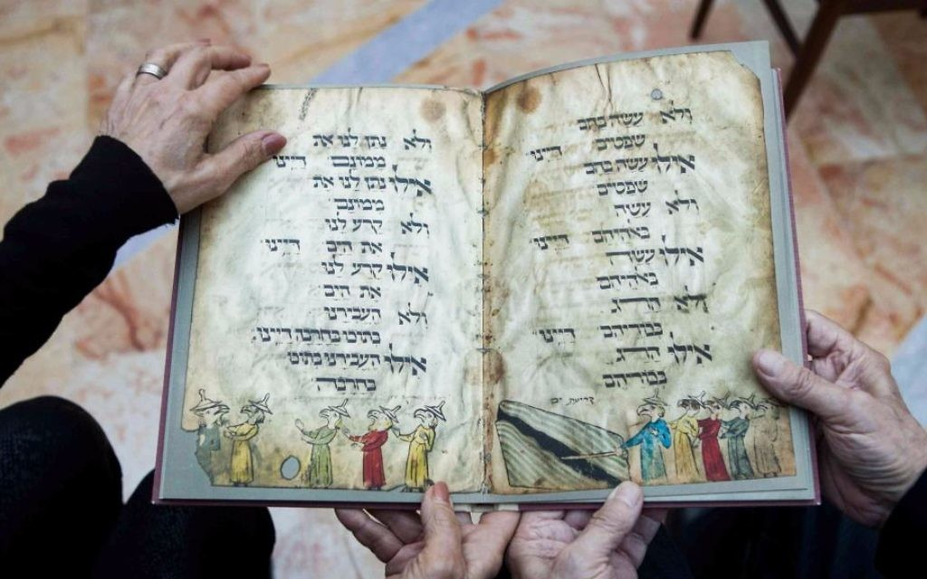 In this file photo taken Wednesday, April 13, 2016, Eli and Shuli Barzilai hold a copy of the Birds' Head Haggadah, the text read around Jewish dinner tables on the Passover holiday, in their home in Jerusalem. (AP Photo/Dan Balilty, File)