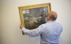 In this photo taken on Wednesday, April 5, 2017, Meir Heller, the Jerusalem lawyer, whose client insists on maintaining his anonymity, holds the Max Liebermann's 'Basket Weavers' painting in a law office in Jerusalem, Wednesday, April 5, 2017.  (AP Photo/Ariel Schalit)