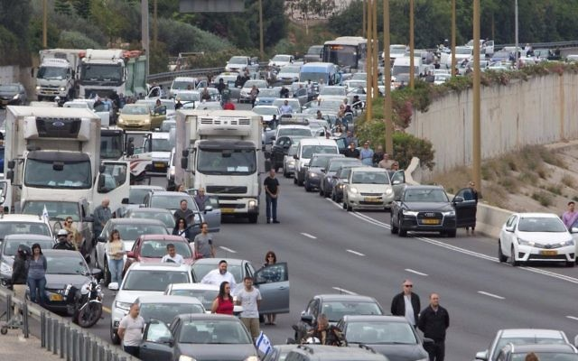 Israelis stand still next to their cars as a siren sounds in memory of victims of the Holocaust, in Tel Aviv, Israel, Monday, April 24, 2017. (AP Photo/Sebastian Scheiner)