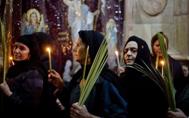 Christians hold candles and palm fonds during the Palm Sunday mass inside the Church of the Holy Sepulchre, traditionally believed by many to be the site of the crucifixion and burial of Jesus, in Jerusalem's Old City, April 9, 2017 during Palm Sunday. (AP Photo/Ariel Schalit)