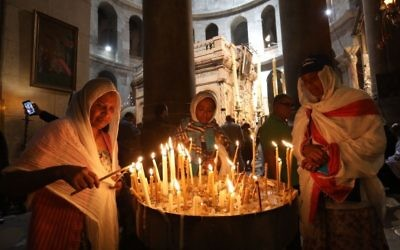 Christian pilgrims light candles inside the Holy Sepulchre church during Good Friday in Jerusalem Friday, April 14, 2017. (Dan Balilty/AP)