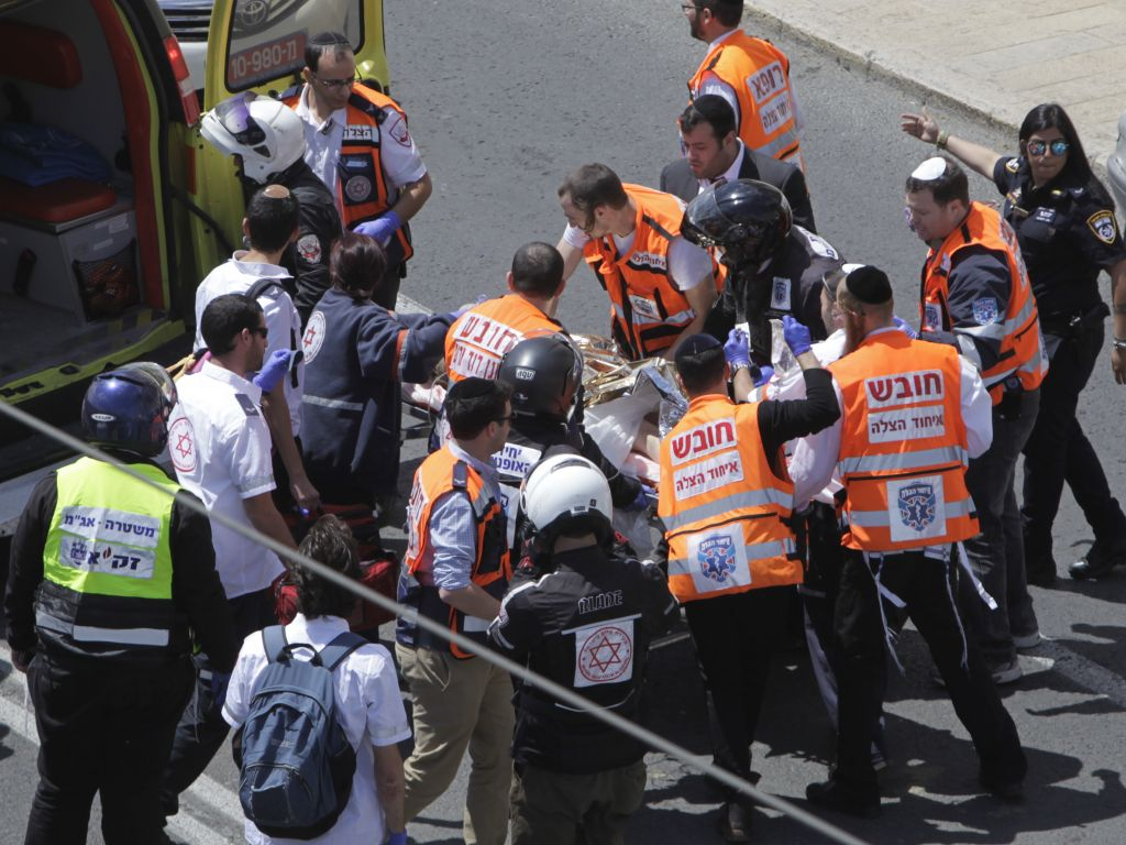 Emergency services evacuate an injured person from the scene of an stabbing attack in Jerusalem Friday, April 14, 2017. Israeli police said a Palestinian man stabbed a woman in Jerusalem, seriously wounding her before forces apprehended him at the scene. She later died. (AP Photo/Mahmoud Illean)