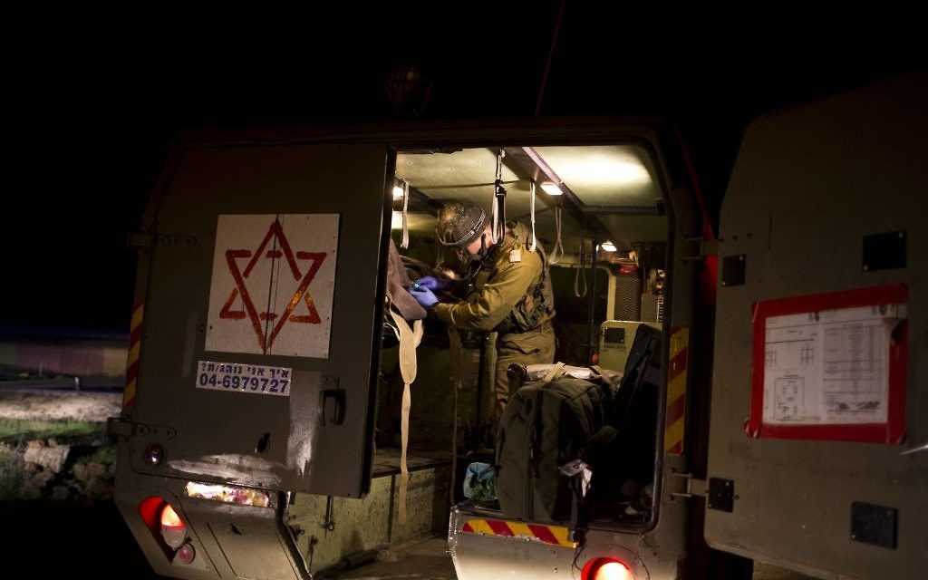 Israeli military medics assist wounded Syrians on April 6, 2017 in a military ambulance. (AP Photo/Dusan Vranic)