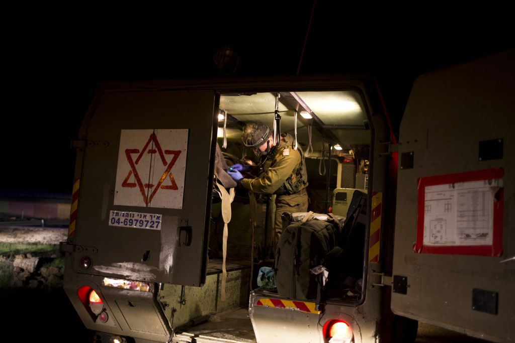 Israeli military medics assist wounded Syrians on April 6, 2017. Seven wounded Syrians who crossed into Israel on Thursday night received immediate treatment and were hospitalized. They are the latest group of Syrians receiving free medical care through an Israeli military program operating since 2013. (AP Photo/Dusan Vranic)