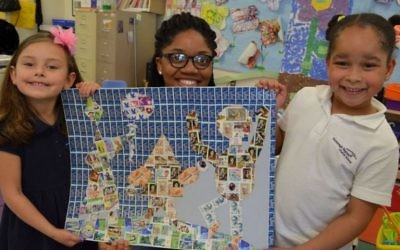 Students at the Foxboro Regional Charter School in Massachusetts pose with a Holocaust-related mural in 2016, created through the school's Holocaust Stamps Project (Courtesy)