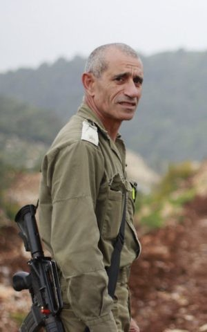 Maj. Eliyahu Gabay stands on a berm near the Lebanese border at kibbutz Hanita on March 22, 2017. (Judah Ari Gross/Times of Israel)