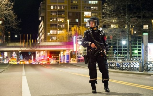 "An officer stands guard as police cordon off a large area around a subway station on a busy commercial street Saturday night, April 8, 2017, after finding what they described as a ""bomb-like"" device, in Oslo, Norway. (Fredrik Varfjell /NTB scanpix via AP)"