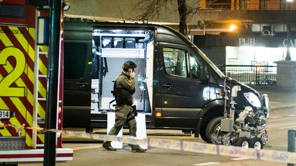"An officer works the scene as police cordon off a large area around a subway station on a busy commercial street Saturday night, April 8, 2017, after finding what they described as a ""bomb-like"" device, in Oslo, Norway. (Fredrik Varfjell/NTB scanpix via AP)"