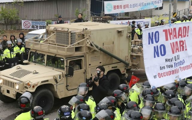 A US military vehicle moves past banners opposing a plan to deploy an advanced US missile defense system called Terminal High-Altitude Area Defense, or THAAD, as South Korean police officers stand guard in Seongju, South Korea, Wednesday, April 26, 2017. (Kim Jun-hum/Yonhap via AP)