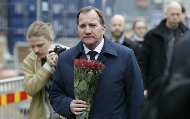Sweden's Prime Minister Stefan Lofven arrives with flowers at a fence near the department store Ahlens, following a suspected terror attack in central Stockholm, Sweden, Saturday, April 8, 2017. (AP Photo/Markus Schreiber)