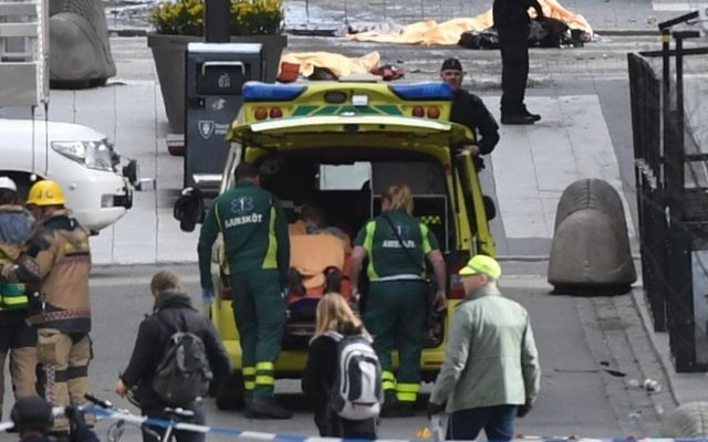 Emergency personnel load a person into an ambulance, center, at the scene after a truck crashed into a department store injuring several people in central Stockholm, Sweden, Friday, April 7, 2017.  (Fredrik Sandberg/TT News Agency via AP)