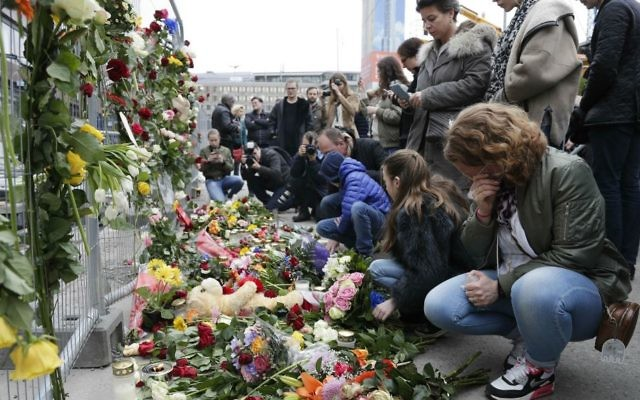 People lay down flowers at a fence near the department store Ahlens following a suspected terror attack in central Stockholm, Sweden, Saturday, April 8, 2017. (AP Photo/Markus Schreiber)