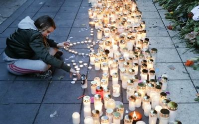 A girl lights candles in front of the department store Ahlens in Stockholm, Sweden, Sunday, April 9, 2017. (AP Photo/Markus Schreiber)