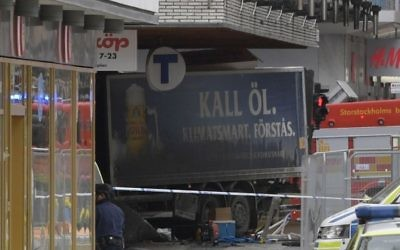 The rear of a truck, left, protrudes after it crashed into a department store killing several people in central Stockholm, Sweden, Friday April 7, 2017. (Anders Wiklund , TT News Agency via AP)
