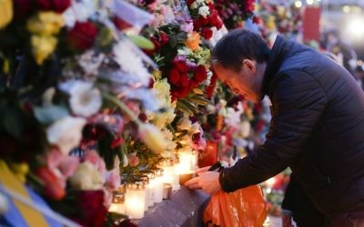 A man lights a candle at a fence near the department store Ahlens, Saturday, April 8, 2017, following Friday's suspected terror attack in central Stockholm, Sweden. (AP Photo/Markus Schreiber)