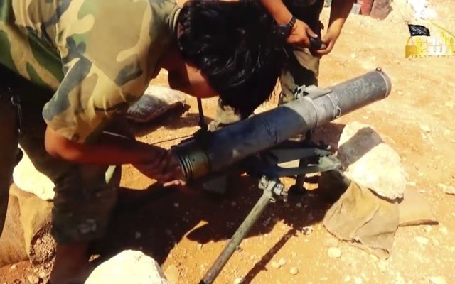 This frame grab from video provided in August 6, 2016, by Turkistan Islamic Party, a militant website outlet that is consistent with independent AP reporting, shows a fighter from the Turkistan Islamic Party prepares to fire a missile, during a battle against the Syrian government forces, in Aleppo, Syria. ( Militant Website Turkistan Islamic Party, via AP)