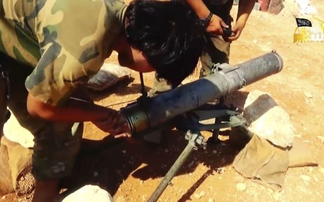 This frame grab from video provided in August 6, 2016, by the Turkistan Islamic Party shows a fighter from the militant group preparing to fire a missile during a battle against Syrian government forces in Aleppo, Syria. (Turkistan Islamic Party website via AP)
