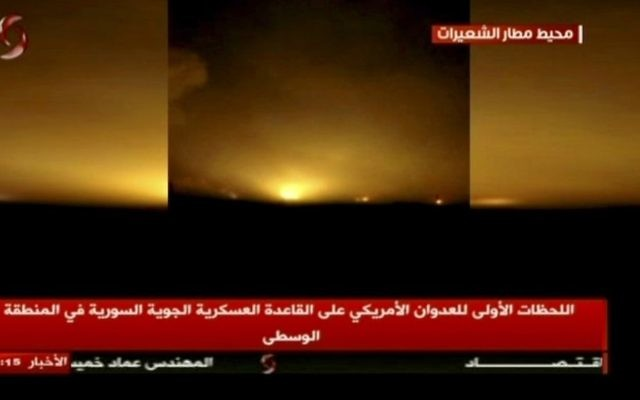 This frame grab from video provided by Ikhbaria TV, a Syrian pro-government TV channel that is consistent with independent AP reporting, shows flames rising from US Tomahawk missiles which hit the Shayrat air base, southeast of Homs, Syria, early Friday April, 7, 2017. The Arabic on the screen reads: 'Around the Shayrat airport, top right, the first moments of the American aggression on the air base in the central region, center bottom.' (Ikhbaria TV, via AP)