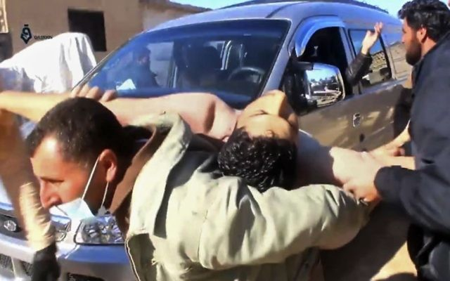 This frame grab from video provided on Tuesday April 4, 2017, by Qasioun News Agency, shows a Syrian man carrying a man on his back who has suffered from a suspected chemical attack, in the town of Khan Sheikhoun, northern Idlib province, Syria (Qasioun News Agency, via AP)