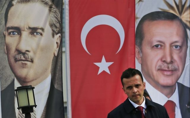 In this Monday, April 3, 2017 photo, backdropped by banners showing modern Turkey's founder Mustafa Kemal Ataturk, left and Turkey's current President Recep Tayyip Erdogan, right, a member of security for Erdogan stands guard following his speech at a rally in his hometown Black Sea city of Rize, Turkey. Turkey is heading toward a historic referendum on Sunday April 16, 2017, with voters deciding whether to approve constitutional amendments that would replace the parliamentary system by a presidential one, scrapping the office of the prime minister and handing over its powers to Erdogan. (AP Photo/Lefteris Pitarakis)