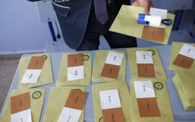 """A man stands over ballots inside a polling station in Istanbul. The ballots read in Turkish: 'Yes"""" in white, and """"No"""", in brown. Voting on extending presidential powers was held in Turkey on April 16, 2017. (AP/Emrah Gurel)"""