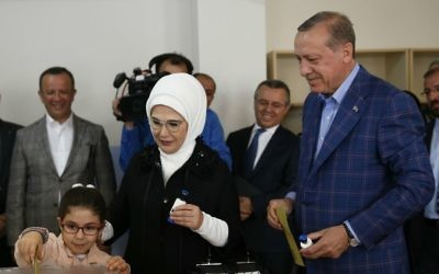 Turkey's President Recep Tayyip Erdogan, right, and his wife Emine, center, look at their granddaughter Mahinur as she casts a ballot inside a polling station in Istanbul, Turkey, on Sunday, April 16, 2017.  (AP Photo/Lefteris Pitarakis)