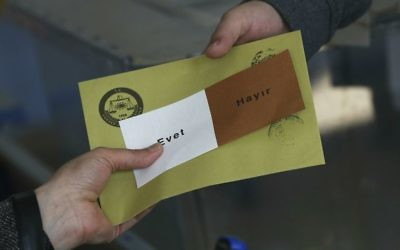 A ballot is handed to a voter inside a polling station in Ankara, Turkey, on Sunday, April 16, 2017. (AP Photo/Emrah Gurel)