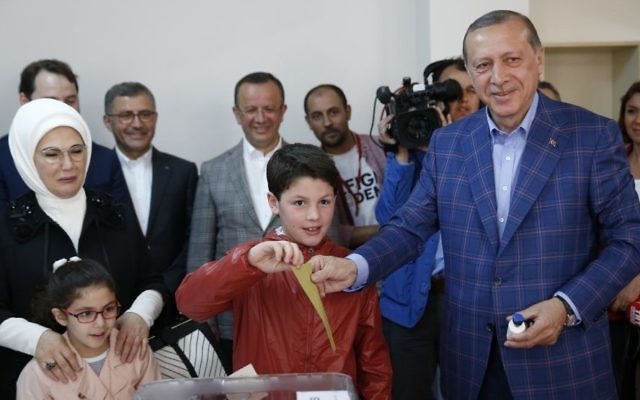 Turkey's President Recep Tayyip Erdogan, right, casts a ballot with his grandson, as wife Emine Erdogan, left, looks on, inside a polling station in Istanbul, Turkey, on Sunday, April 16, 2017. (AP/Lefteris Pitarakis)