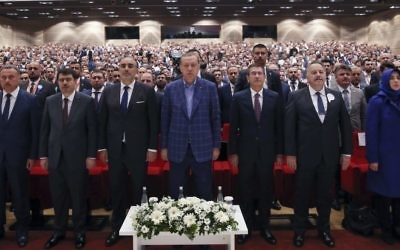 Turkey's President Recep Tayyip Erdogan, center, stands as he listens to the national anthem, prior of delivering a speech at a conference in Istanbul, Saturday, April 29, 2017 (Press Presidency Press Service via AP, Pool)