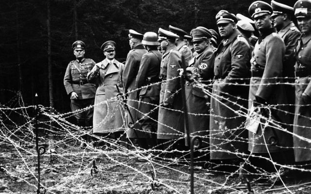 In this Oct. 6, 1938, file photo, Adolf Hitler, second from left, stands in front of the barbed wire fortifications at Kreuzbuche, Germany after German troops advanced and occupied the second zone of Sudetenland.  (AP, File)