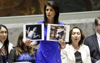 US Ambassador to the UN Nikki Haley shows pictures of Syrian victims of chemical attacks as she addresses a meeting of the Security Council on Syria at UN headquarters on April 5, 2017. (AP Photo/Bebeto Matthews)